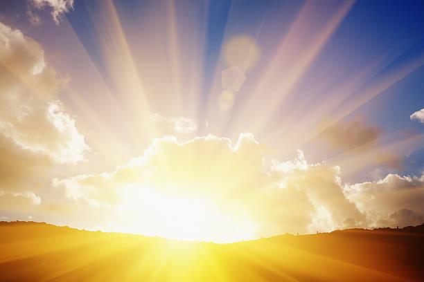 the sun's rays on the horizon flare dramatically through clouds - 明亮 個照片及圖片檔