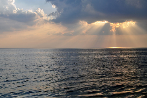 The sun's rays through the clouds above the sea.