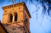 Rome, Italy, January 02 - The warm light of a late afternoon illuminates the ancient bell tower of the Santa Rufina e Seconda church in Trastevere, a district in the heart of the eternal city visited by millions of tourists every year. Image in HD format.