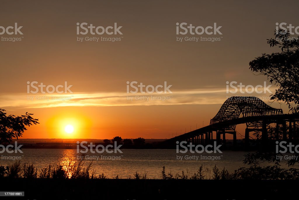 The sunset over the water near a bridge stock photo