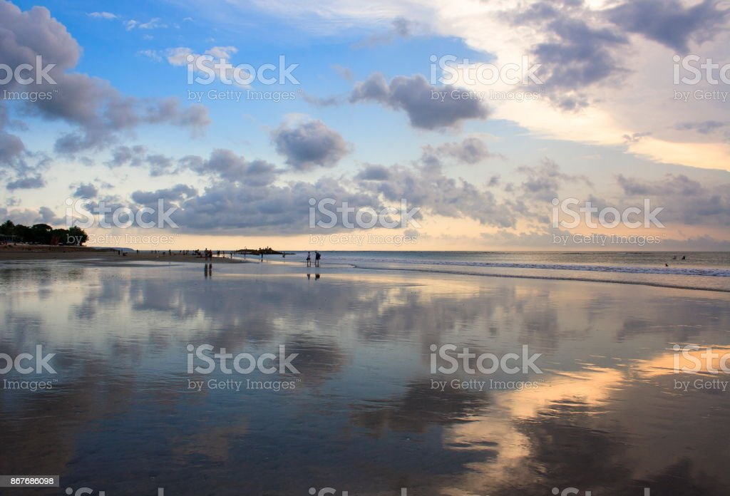 The sunset sky is reflected in the mirror beach of Kuta. stock photo