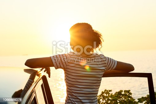Shot of a young woman watching the sun go down on a roadtrip