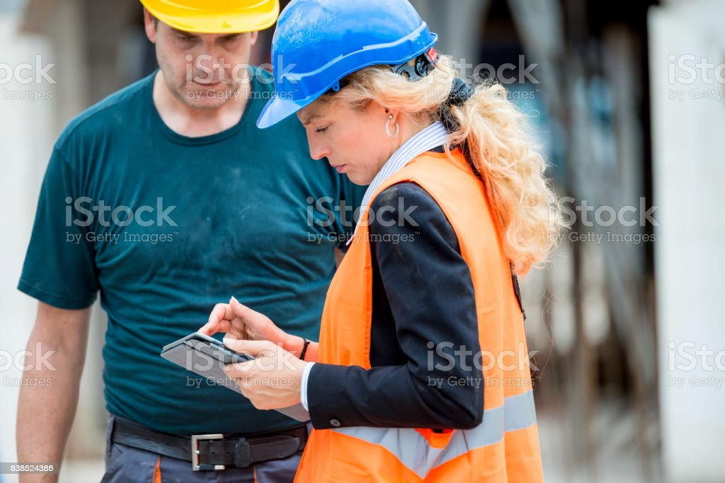 The supervisor and foreman are checking the details on the digital tablet stock photo