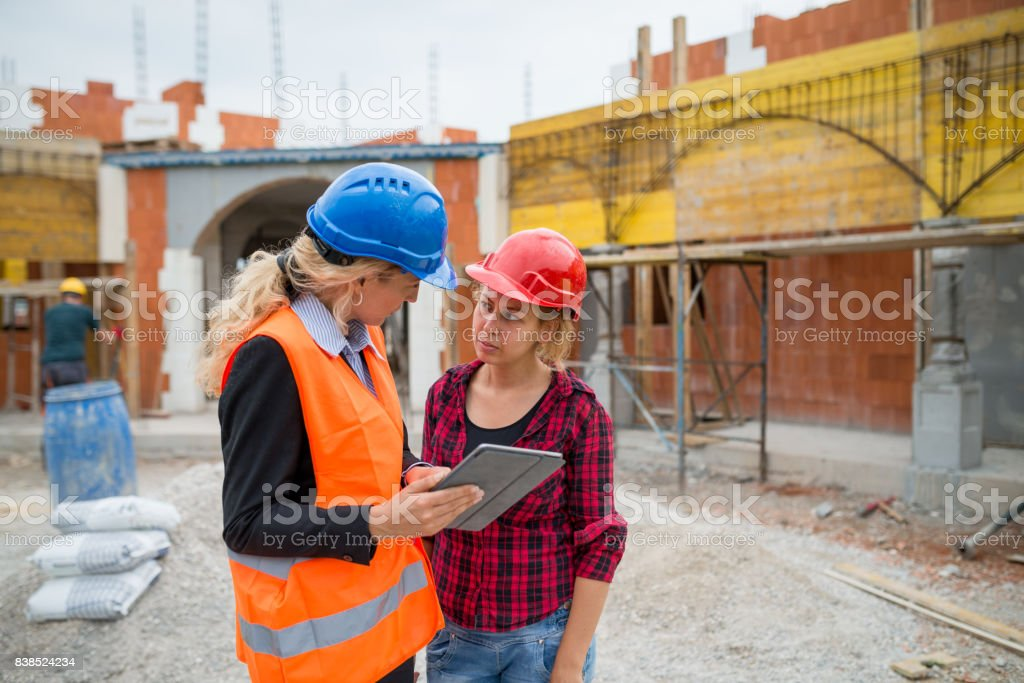The supervisor and her assistant check the details on the digital tablet stock photo