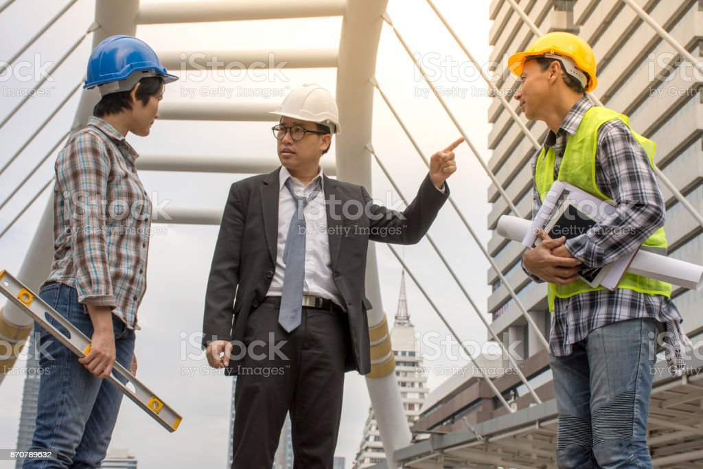 The supervisor is discussing the construction with the Asian staff and the architect stock photo
