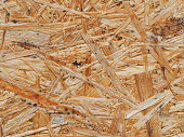 The surface of pressed wood from sawdust close-up. The texture of the chipboard Background. Wood recycling and reuse