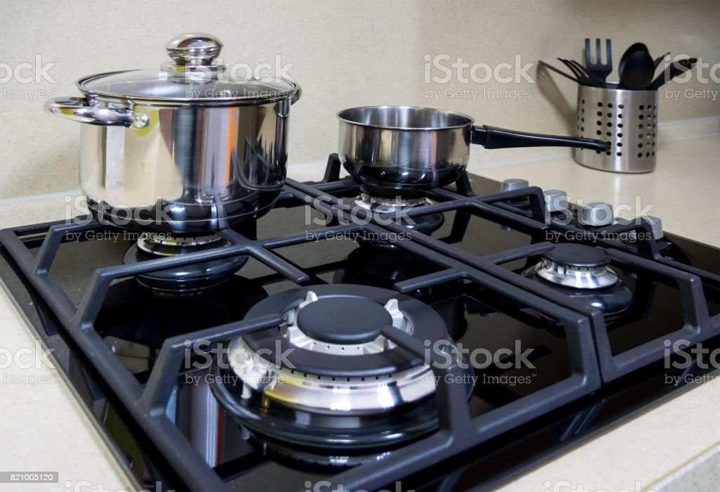The surface of the gas cooker and the dishes standing on it stock photo