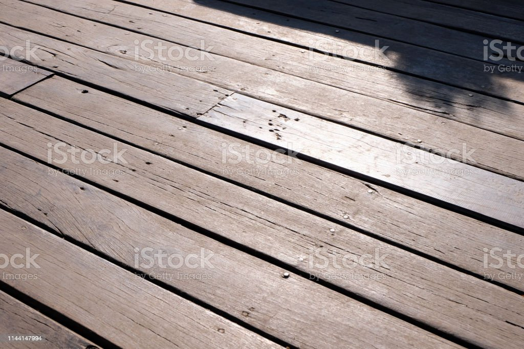 The surface of the unpainted wooden floor with sun shines in...