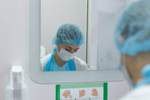 de chirurg wast zijn handen voor de operatie. - mirror mask stockfoto's en -beelden