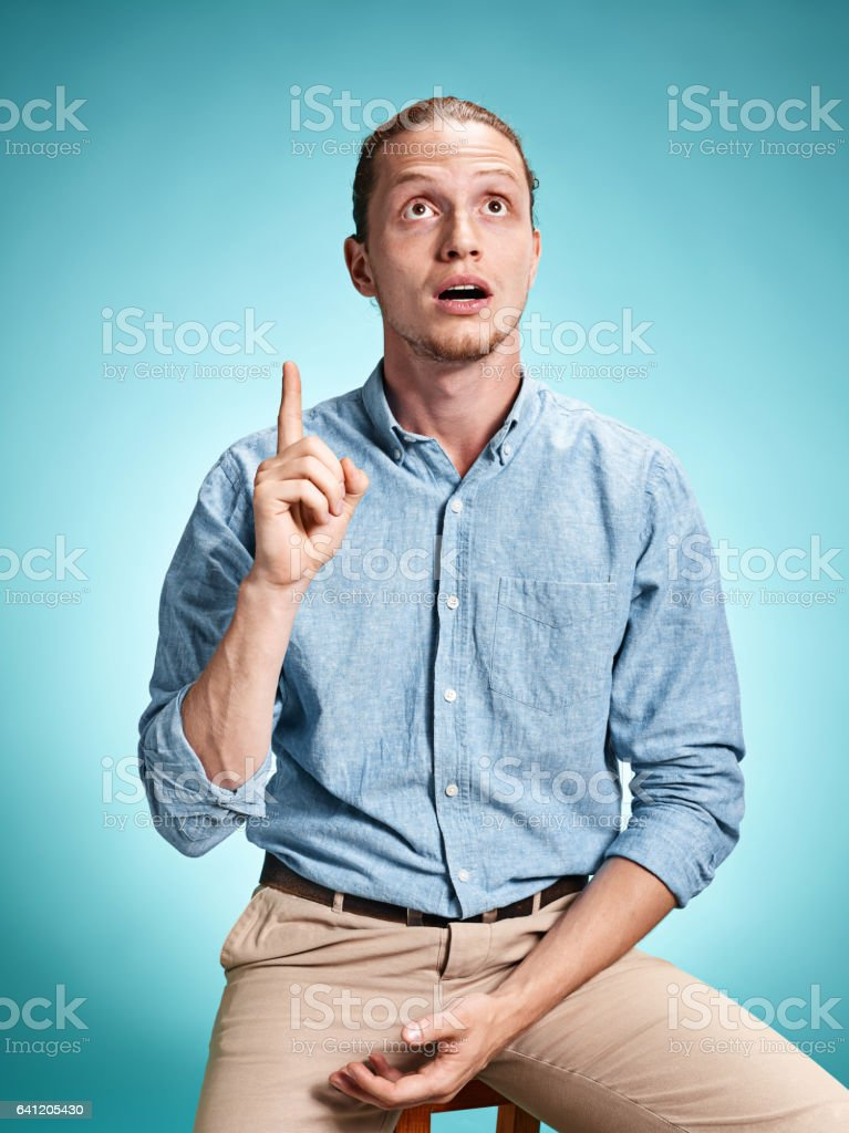 The surprised young man over blue background stock photo