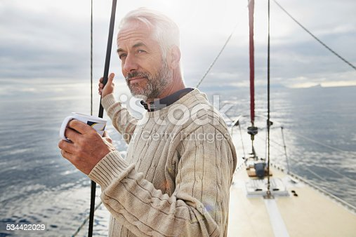 Shot of a mature man on his sailboat drinking a cup of coffee