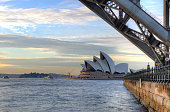 Sydney, Australia - June 23, 2014; View of Sydney Opera House from under the Sydney Harbour Bridge, just after sunrise.