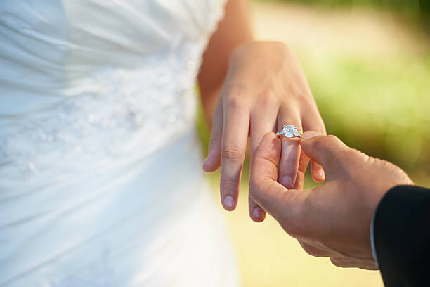 the symbol of their commitment - diamond ring hand stock photos and pictures