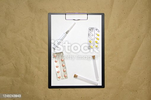1139340462 istock photo The tablet with a clip for the clip of paper with a white sheet a4 lies against the background of craft brown crumpled paper. On top is a medical syringe, pills in a blister and two transparent empty tubes with corks. Place for text, copy space and layout 1245243943