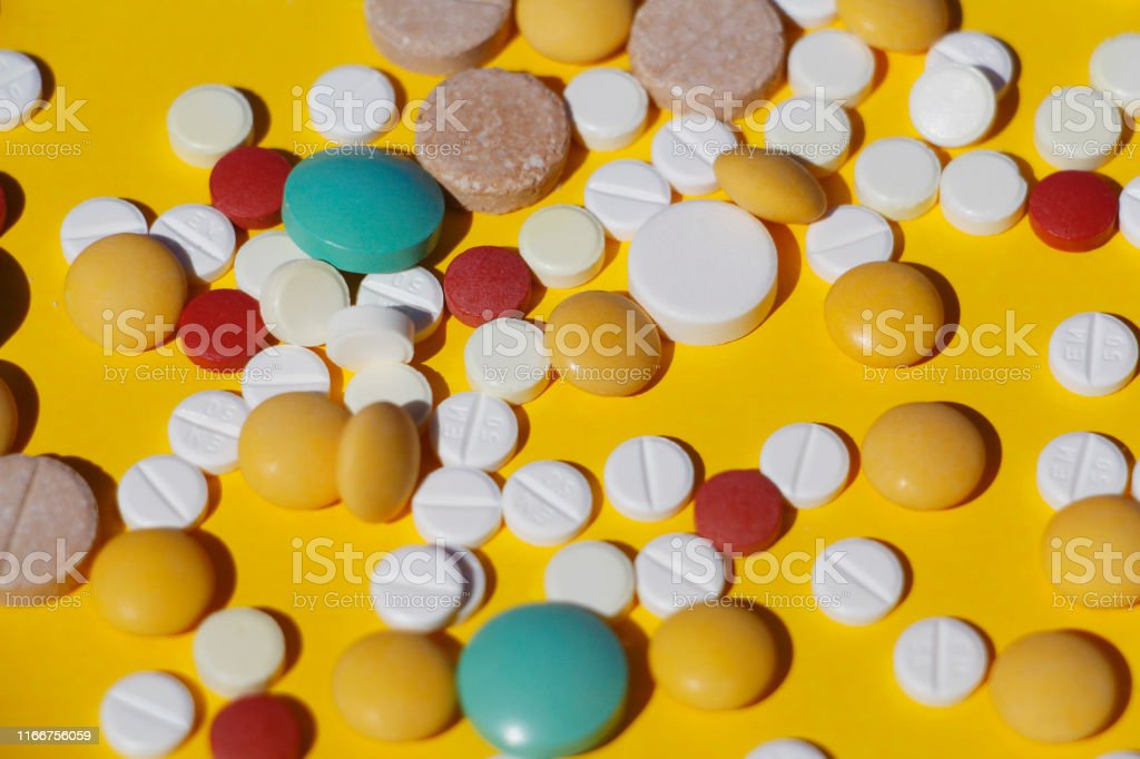A lot of multi-colored pills on a yellow background. The tablets are...