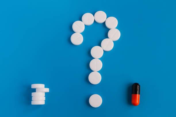 die tabletten sind weiße meds auf blauem grund. ein symbol mit einem fragezeichen versehen. wählen sie zwischen mehreren pillen und medizinische pillen - lieblingsrezepte stock-fotos und bilder