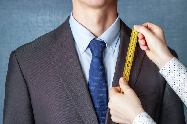 The tailor measures the suit with a measuring tape close-up stock photo