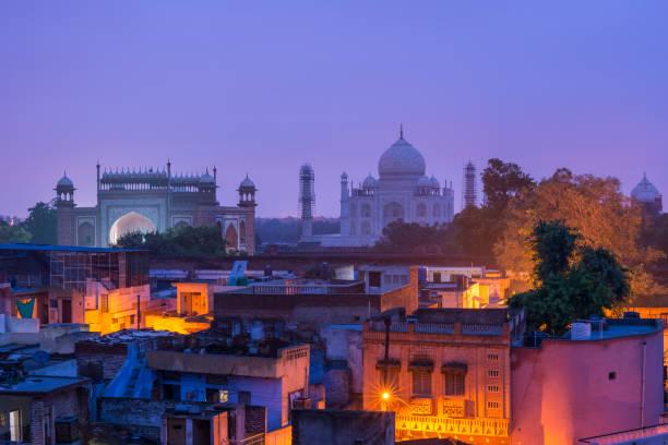 the taj mahal and agra town at dawn - индия стоковые фото и изображения