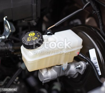 The tank with brake fluid in the car in the engine compartment. The concept of the working brake system, safety, transportation