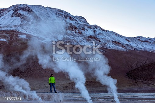 Woman contemplating El Tatio geyser. It is on a field located in the Andes Mountains of northern Chile at 4,320 metres above mean sea level in the desert of Atacama.