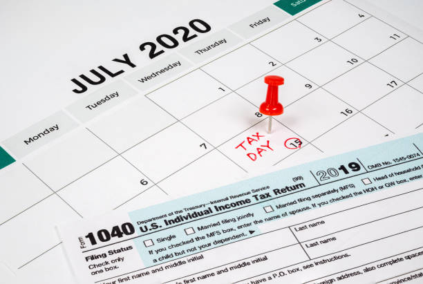 The tax day was extended to July 15th because of Covid-19. July calendar showing 1040 return form and tax day. stock photo