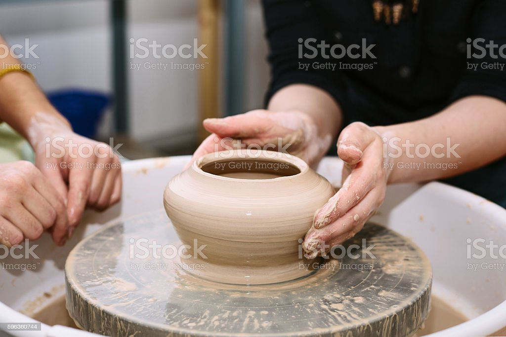 the teacher teaches the student work on the potter's wheel. royalty-free stock photo