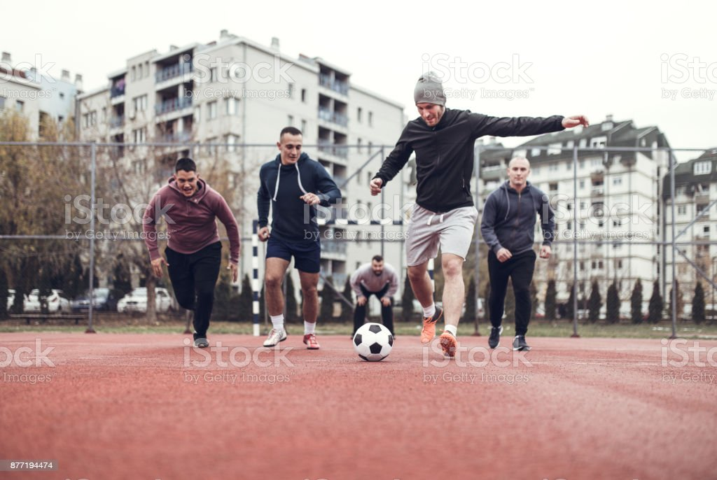 Four people playing football in schoolyard