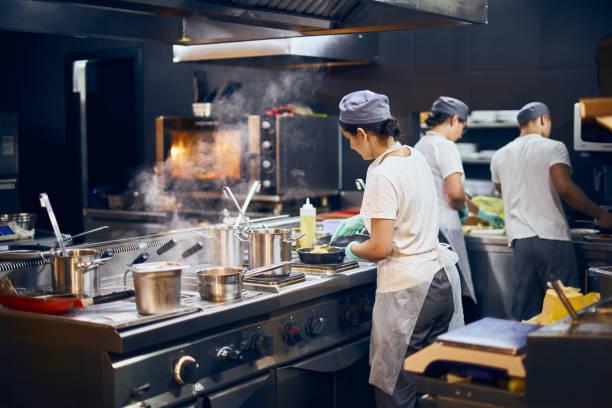 el equipo de cocineros respalda el trabajo en la cocina moderna, el flujo de trabajo del restaurante en la cocina. copiar espacio para texto - restaurante fotografías e imágenes de stock