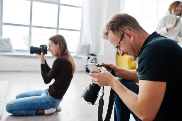 The team of two photographers shooting on studio. Professional photographer on work. stock photo