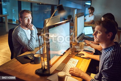 Shot of a group of young people using computers during a late night in a modern office