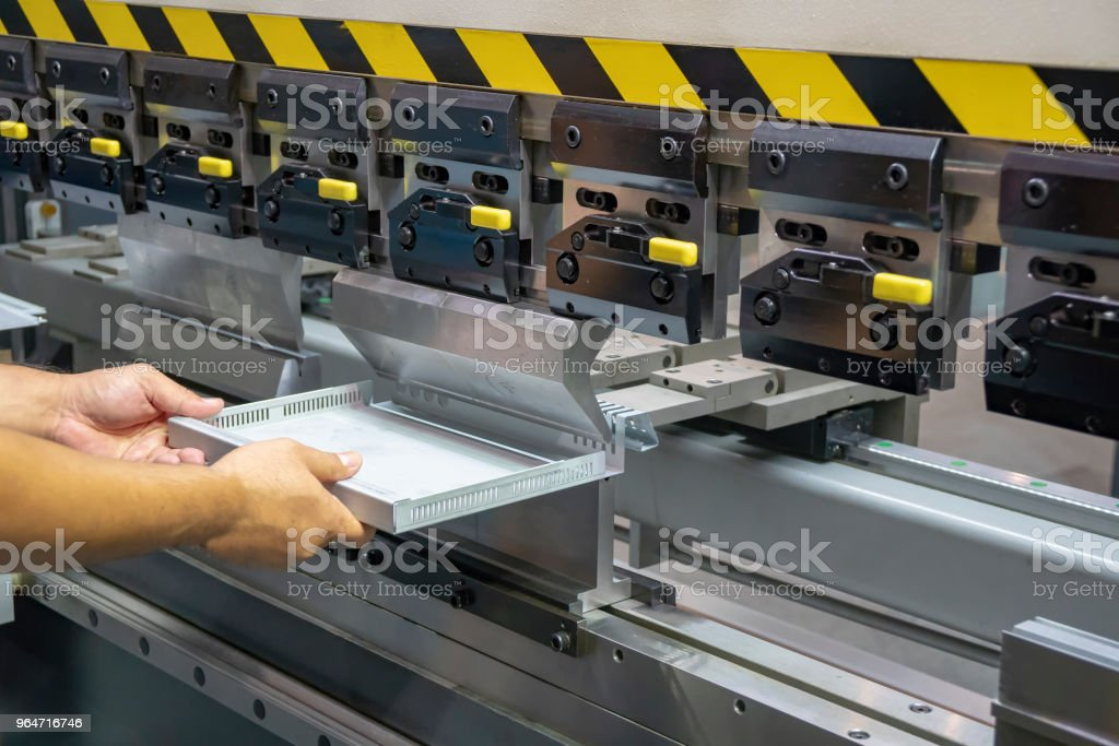 The technician operator handing the sheet metal part with  hydraulic bending machine. royalty-free stock photo
