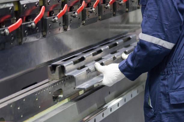 The technician operator use hydraulic bending machine. stock photo