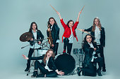 Teen music band performing in a recording studio. The group of girls standing together and posing at camera. Studio portrait of young attractive fashion caucasian teen girls dressed inblack leather jackets grouped together. Kids fashion and rock concept