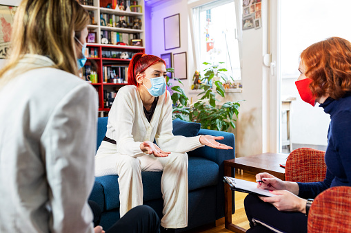 Beautiful teenage girl talking  to a counsellor about interpersonal relationships.They are wearing protective face masks.Psychotherapy during covid 19 pandemic.