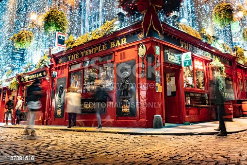The Temple Bar pub in Dublin city centre, popular tourist attraction with christmas lighting and decorations, shot at night with blurred people in long exposure with retro vintage colour grading