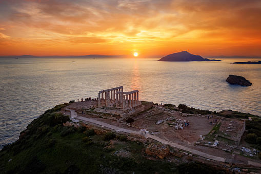 The historic Temple of Poseidon at Cape Sounion, Attica, Greece, during golden sunset time