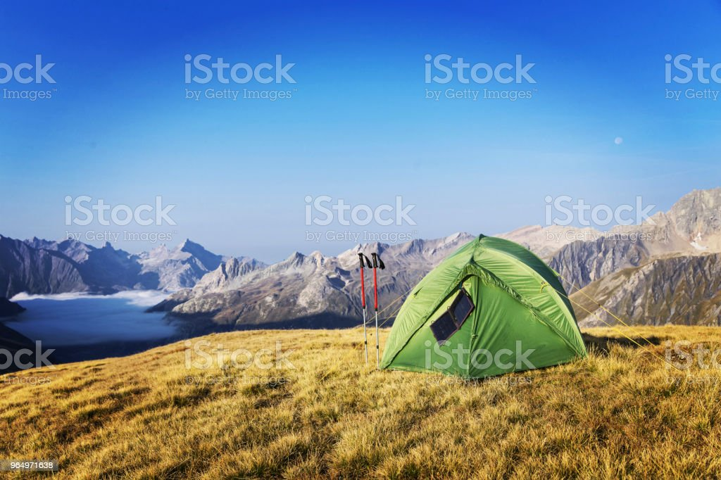 The tent is on top of the mountain. The solar panel hangs on the tent.