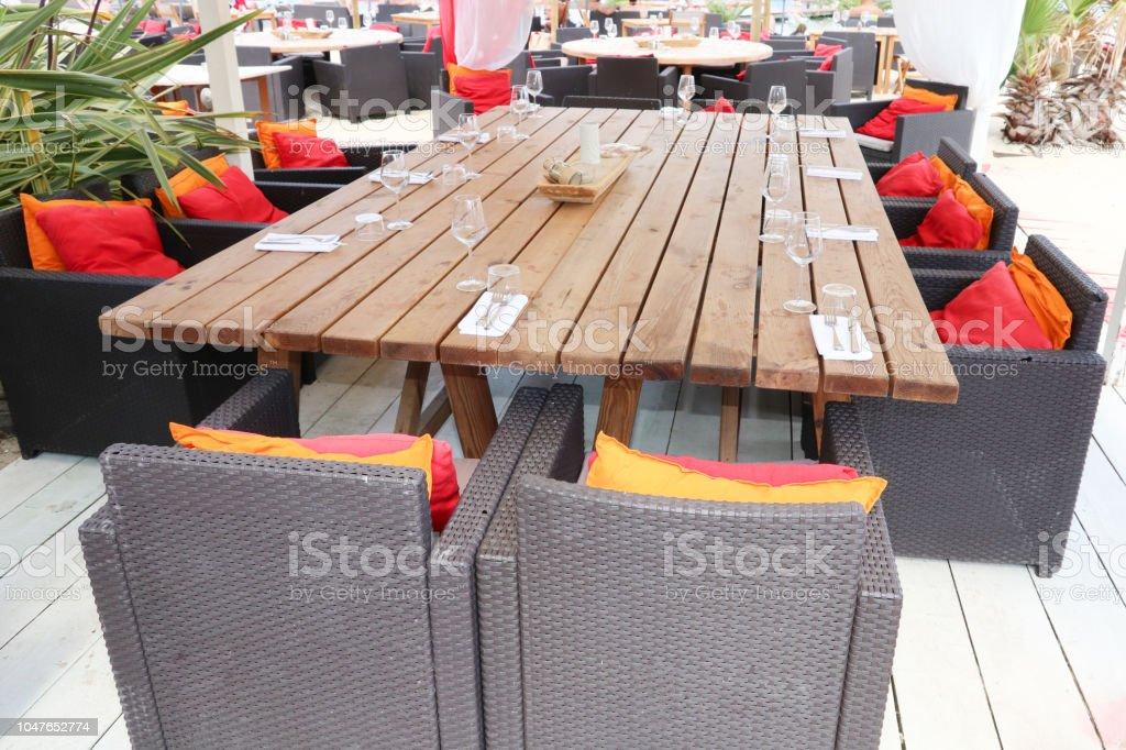 La Terraza De Un Restaurante Con Una Gran Mesa De Madera