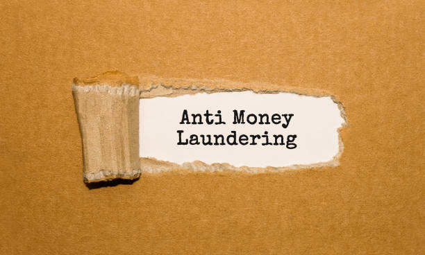 the text anti money laundering appearing behind torn brown paper - defiance stock pictures, royalty-free photos & images