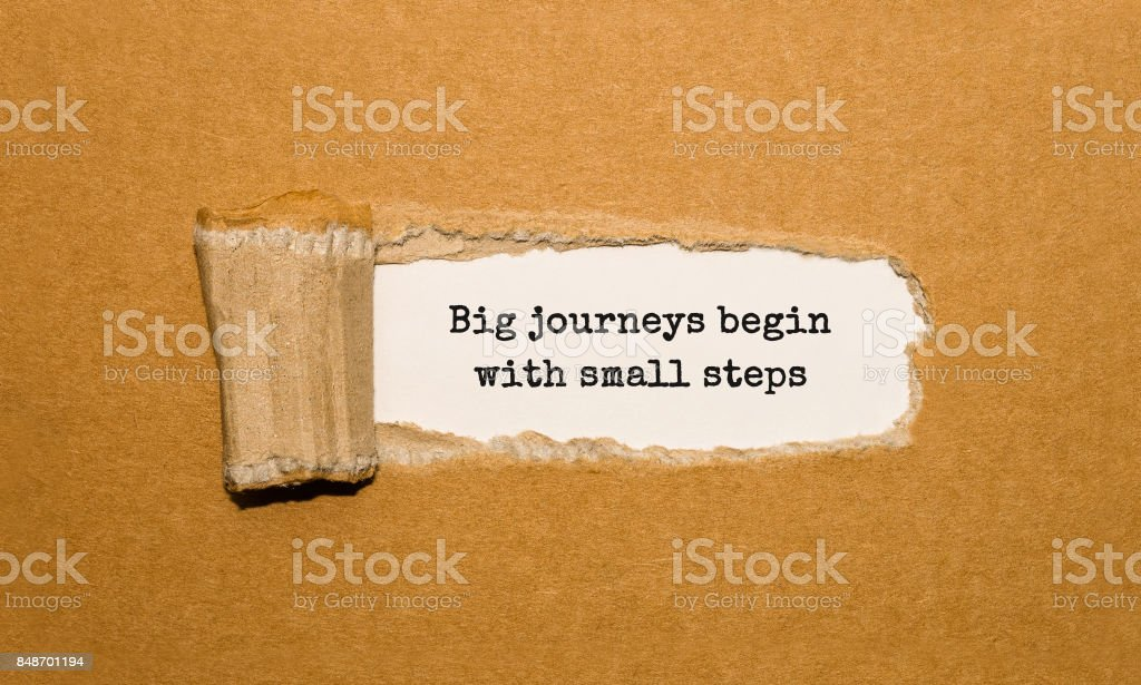 The text Big journeys begin with small steps appearing behind torn brown paper stock photo
