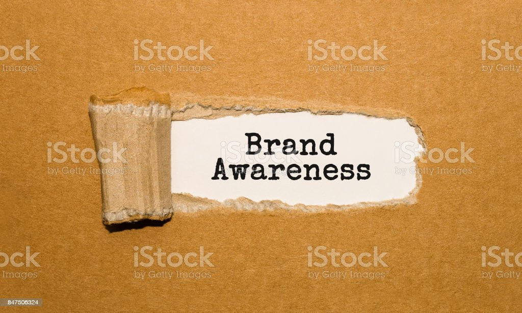 The text Brand Awareness appearing behind torn brown paper stock photo