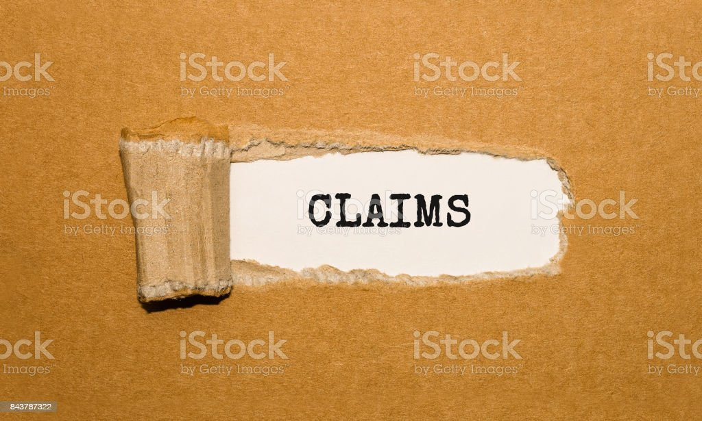 The text Claims appearing behind torn brown paper stock photo