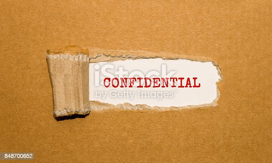 1070355804 istock photo The text CONFIDENTIAL appearing behind torn brown paper 848700652