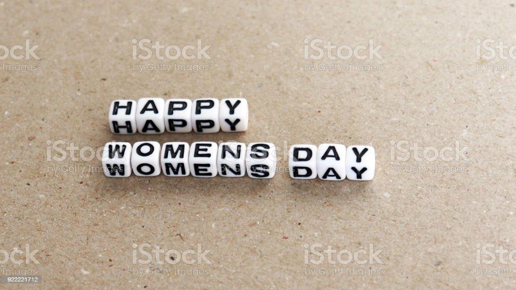 The text HAPPY WOMENS DAY with alphanumeric cube. stock photo