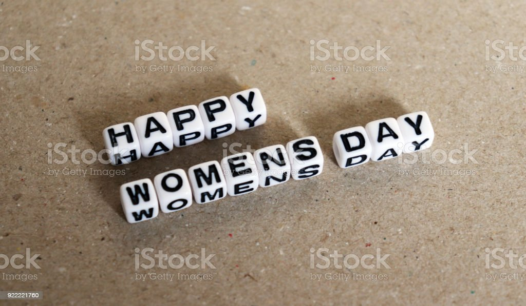 The text HAPPY WOMENS DAY with alphanumeric white cube. stock photo
