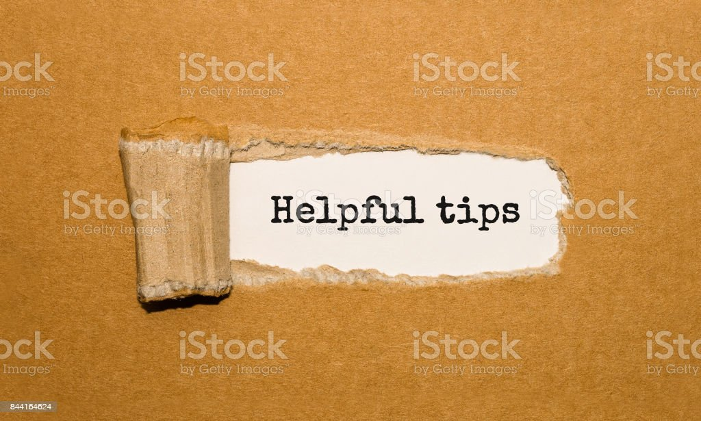The text Helpful tips appearing behind torn brown paper stock photo