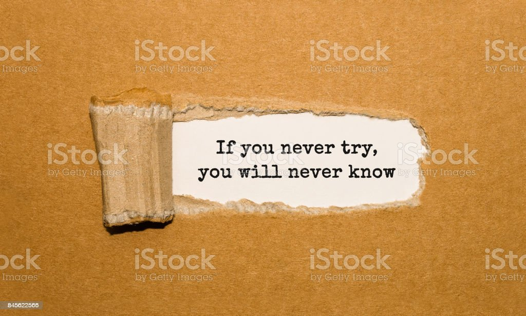 The text If you never try you will never know appearing behind torn brown paper stock photo