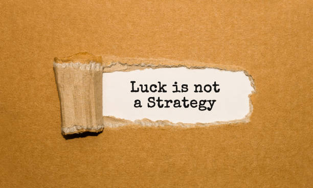 The text Luck is not A Strategy appearing behind torn brown paper stock photo