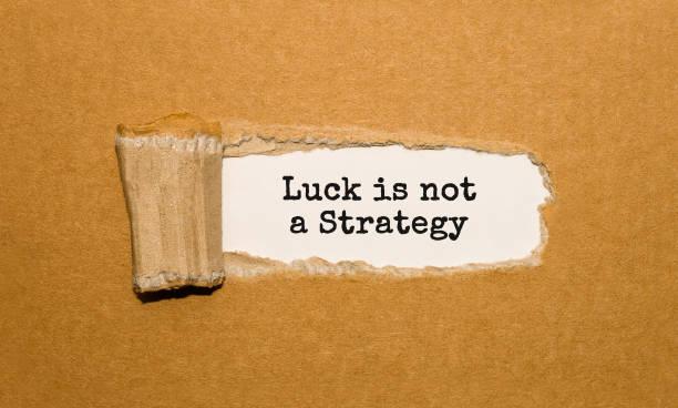 el texto suerte no es una estrategia que aparece detrás de papel rasgado - buena suerte fotografías e imágenes de stock