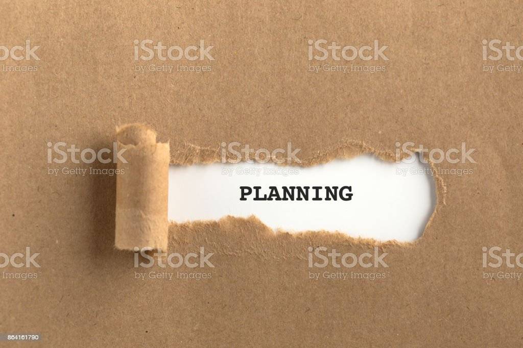 The text PLANNING behind torn brown paper royalty-free stock photo